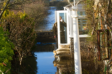 Man standing in doorway of flooded home during January 2014 flooding, Somerset Levels near Langport, Somerset, England, UK, 11th January 2014.