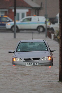 Car in floodwaters after sea defences were breached, at Splash Point in Rhyl, Denbighshire, Wales, 5th December 2013.