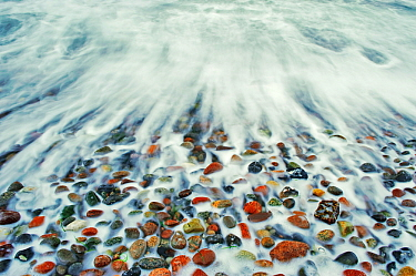 Waves of Baltic Sea washing over and polishing coloured pebbles, Markgrafenheide, Mecklenburg-Vorpommern, Germany, January