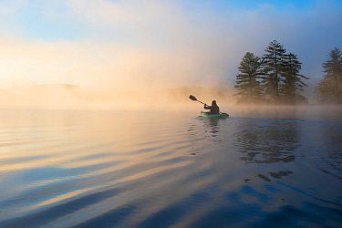 Kayaking at dawn. Grafton Pond, Enfield, New Hampshire, United States. Model released.