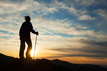 Walker silhouetted at sunset on Braeriach, Cairngorms National Park, Scotland, UK.November