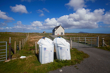 Nitrogen fertilzer in bags, ready for application to machair, coastal grazing habitat. Outer Hebrides. Scotland, UK, June.