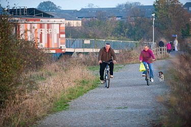 Two cyclists with dog, Rainham Marshes RSPB reserve, Essex, England, UK, November