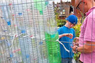 Man and boy making bird scarers from plastic bottles in a community vegetable garden on the roof of Budgens Supermarket, Food from the Sky initiative, Crouch End, London, England, UK, August 2011