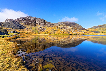 Lake Cwmorthin looking south west showing spoil heaps and ruined cottages of the disused slate mine with pieces of slate covering the bed of the lake in the foreground near Blaenau Ffestiniog, North W...