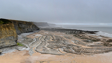 Faulted Jurassic age Liassic limestones (Blue Lias) exposed in the cliffs and on the foreshore. Southerndown, South Glamorgan Heritage Coast, Wales, UK. September