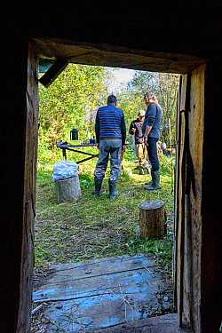 View through door of people talking, whilst on diving expedition. Upper reaches of the Lena River Baikalo-Lensky Reserve, Siberia, Russia. August 2018.
