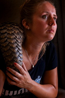 Young orphaned Temminck's ground pangolin (Smutsia temminckii) rests on the shoulder of vet and pangolin foster mother Jade Aldridge at the Rhino Revolution rehabilitation facility in South Africa...