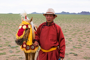Horse trainer standing with race winning horse. Naadam festival, Great Gobi B Strictly Protected Area, Mongolia. August 2018.