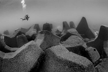 Diver close to wave breaker concrete blocks, Xiaoliuqiu Island, Taiwan