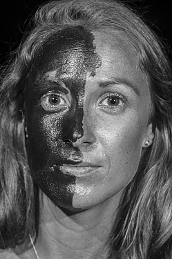 Woman with sunscreen applied to one side of face, portrait under UV light. 2016.