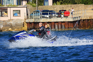 Man and woman on jet ski with harbour wall beyond. Poole Harbour, Dorset, England, UK. September 2018.
