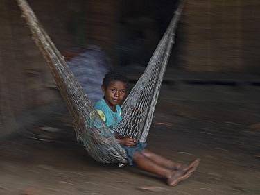 Boy swinging on hammock. Nara village, Makira Island, Solomon Islands. 2018.