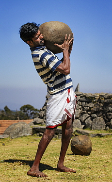 Man of the Toda tribe lifting a heavy stone to show he is ready for marriage. Nilgiri Mountains, Tamil Nadu, India. 2014.