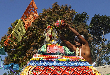 Man pouring holy water over top of temple in Kumbhabhishekam, a Hindu ritual. Pandalur, Tamil Nadu, India. 2014.