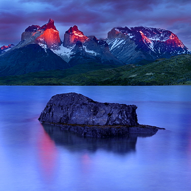Central Massif and towers of Torres del Paine National Park at sunrise, island reflected in Lago Pehoe in foreground. Patagonia, Chile. November 2018.