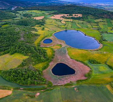Lagoons of Gayangos with surrounding countryside of woodlands and fields, aerial view. Merindad de Montija, Burgos, Castile and Leon, Spain. June 2019.