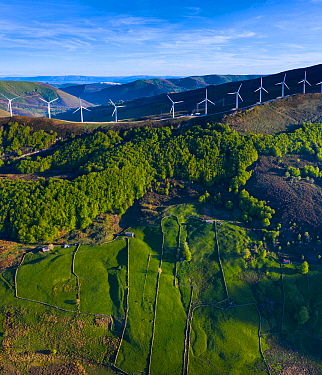 Wind turbines on ridge of hill, Beech (Fagus sp) forest and fields bordered by stone walls on hillside below. Aerial view in evening light. Portillo de la Sia, Soba Valley, Valles Pasiegos, Cantabria,...