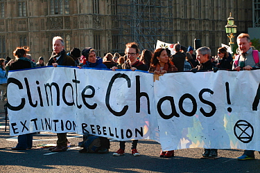 Protestors holding 'Climate chaos!' banner at Extinction Rebellion climate change demonstration. London, England, UK. 17 November 2019.