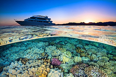 Split level photograph of a liveaboard dive boat (M.Y. Whirlwind), anchored near a coral reef, at sunet. Ras Katy, Sharm El Sheikh, Sinai, Egypt. Red Sea