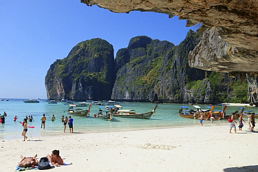Tourists and boats at Maya Beach, limestone rock cliffs in background. Koh Phi Phi Leh, Krabi Province, Thailand. 2015.