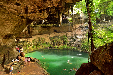 The Zaci cenote with people swimming, in the middle of Valladolid, Yucatan peninsula, Mexico.