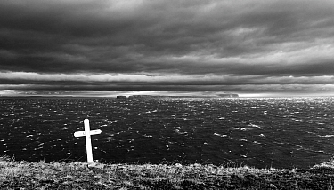 Stormy seas and cross on a grave. In background is the Malmey island. Iceland 2016