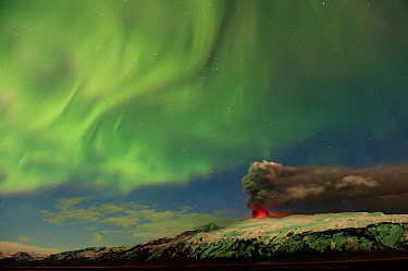 Subglacial volcanic eruption under the Eyjafjallajokull ice cap with northern lights above the ash plume at night, Iceland, April 2010