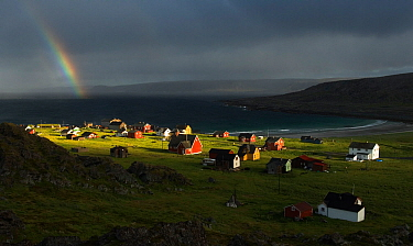 Rainbow over Hamningberg, with dark sky in background and bright light shining on village, Varanger, Finnmark, Norway. July 2006.