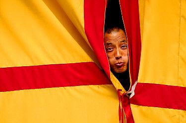 Monk peering through curtains, making a face, Hemis Buddhist Monastery, 3670 meters of altitude, Ladakh, India. September 2011.