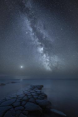 Milky Way over sea at Kimmeridge Ledges, Kimmeridge Bay, Jurassic Coast World Heritage Site, Dorset, England, UK, August.
