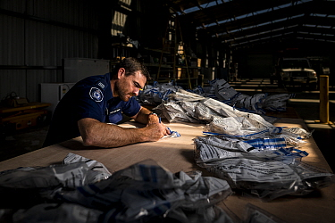 ?Glenn Lineham, a Victoria Wildlife Officer from the Department of Land, Water and Planning (DEWLP), sorts through and documents evidence bags from 406 poisoned Wedge-tailed eagles (Aquila audax) as p...