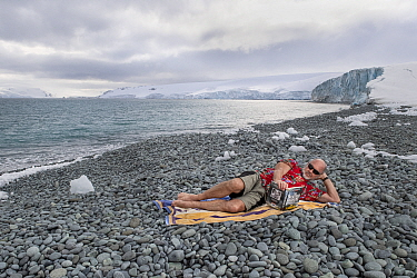 Tim Flannery in summer clothing, reading his best-selling book 'The Weather Makers' on an icy pebble beach, Robert Point, Antarctic Peninsula, Antarctica?, to illustrate the warming of the Ant...