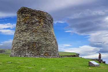 Tourist visiting Mousa Broch, tallest Iron Age broch and one of Europe's best-preserved prehistoric buildings, Shetland Islands, Scotland, UK. June 2018. Digital composite