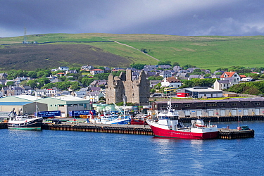 View over Scalloway Castle, museum and fishing boats in the harbour of the village Scalloway on the Mainland, Shetland Islands, Scotland, UK. June 2018