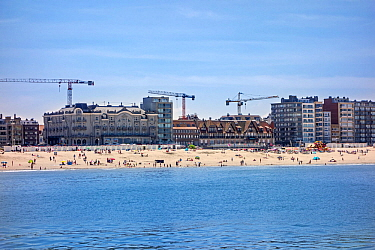 Tourists on the beach and flats and apartments being built at Nieuport / Nieuwpoort, seaside resort along the North Sea coast, West Flanders, Belgium 2019