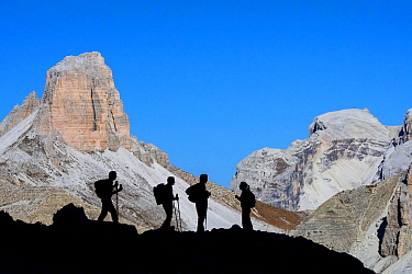 Four mountain climbers silhouetted against Torre dei Scarperi / Schwabenalpenkopf, Sexten Dolomites, Parco Naturale Tre Cime, South Tyrol, Italy, October 2019