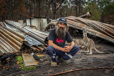 Joseph Henderson, one of the founders and managers of Wallabia Wildlife Shelter, in front of the burnt remains of his house, which was destroyed (along with the animal enclosures) during the 2019/20 b...