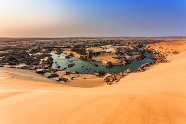 The Kunene River is the natural border between Namibia (south) and Angola (north). The Kunene River stops the sand dunes coming from the south, pushed by the strong wind. Skeleton Coast National Park,...