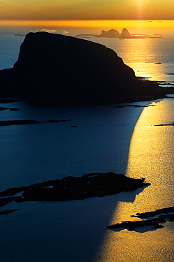 Aerial view of islands, scattered in a wide strandflat. Setting sun reflecting in the sea. Lovund and Traena, Helgeland Archipelago, Norway. July.