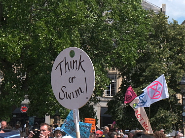 'Think or swim!' placard at Extinction Rebellion climate change protest. Bristol, England, UK. 16 July 2019.