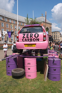 Pink car emblazoned with 'Zero carbon', on top of oil drums. Extinction Rebellion climate change rally. Bristol, England, UK. 16 July 2019.