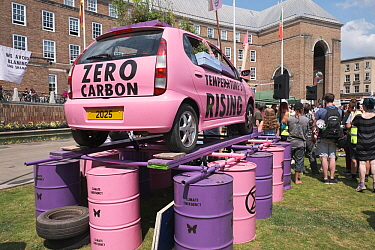 Pink car emblazoned with 'Zero carbon' and 'Temperature's rising', on top of oil drums. Extinction Rebellion climate change rally. Bristol, England, UK. 16 July 2019.