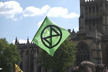 Extinction Rebellion logo on flag. Climate change protest march, Bristol, England, UK. 16 July 2019.
