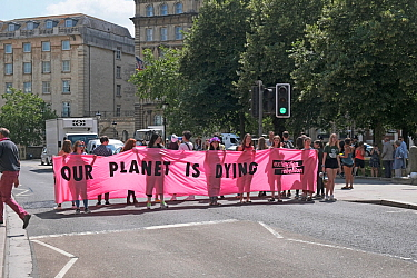 School children stopping traffic by blockading a pedestrian crossing for seven minutes at a time, holding part of 'The youth are crying our planet is dying' banner. On day of Extinction Rebell...