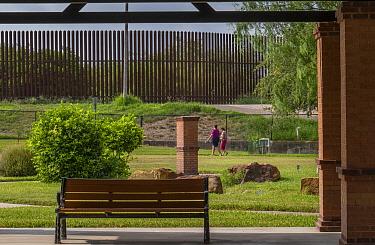 Grounds of Old Hidalgo Pump House and World Birding Center, border wall in background. Near the Rio Grande, Hidalgo County, Texas, USA. July 2019.