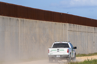 Border patrol driving on no-man's land side of 30 foot concrete and steel border wall. On private farm, Mission, Hidalgo County, Texas, USA. 2019.
