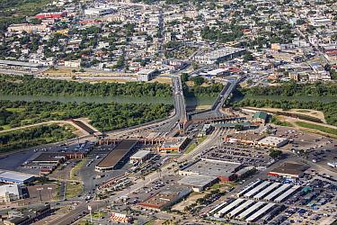 Aerial view of border crossing over Rio Grande towards Tamaulipas, Mexico. Border wall in Hidalgo County, Texas, USA. July 2019.