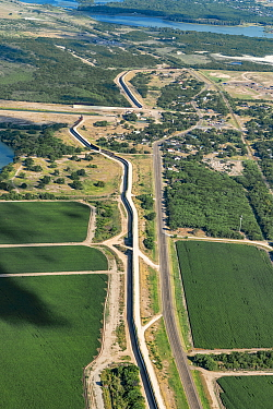 Border wall through agricultural land in Rio Grande Valley, aerial view. Mission, Hidalgo County, Texas, USA. July 2019.