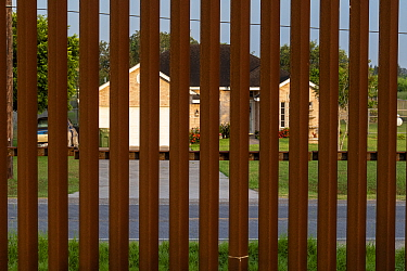 House viewed through border wall. Southmost Preserve, Nature Conservancy Reserve, Brownsville, Texas, USA. 2019.